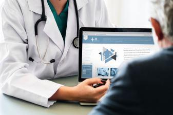 Ärztin erklärt einem Patienten etwas auf einem Laptop